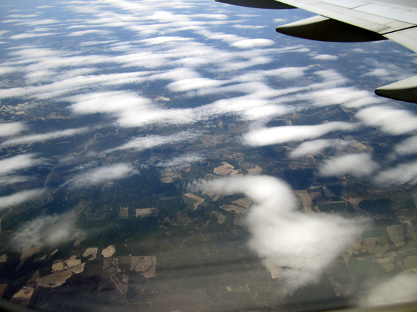 Green trees and fields are visible through the layer of whispy white clouds
